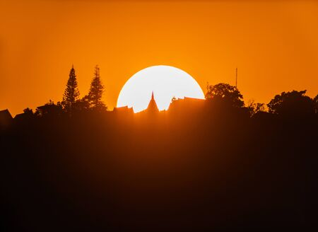 Big sun on sunset and Silhouette Wat Phra That Doi Suthep temple on top mountain  of Chiang Mai, Thailand, Asia.