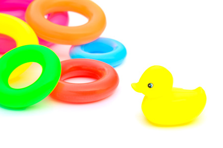dabbling duck: Yellow rubber duck and swimming rings on white Background.