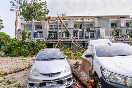 wind down: THAILAND, CHIANG MAI - MAY 17: Damage building and cars by falling trees after hard rain storm in Sarapee of Chiang Mai, Thailand on May 17, 2016.