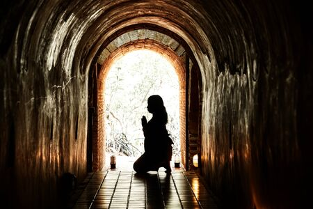 protection of the bible: Silhouette of woman praying in tunnel