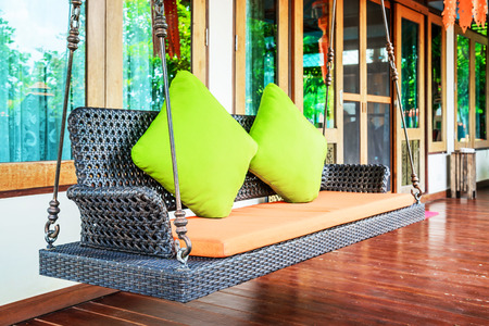 Plastic wicker porch swinging bench with green pillows and orange seat. Stock Photo