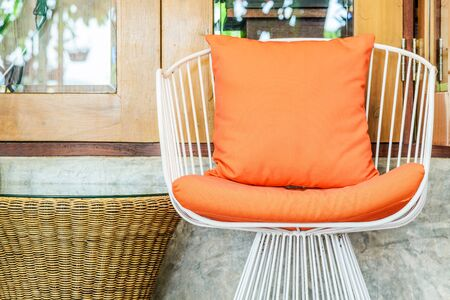 orange chairs: Iron chairs with orange pillows