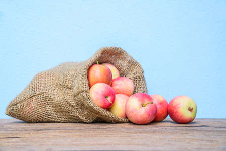 Fresh apples with a cloth sack bag on wood table