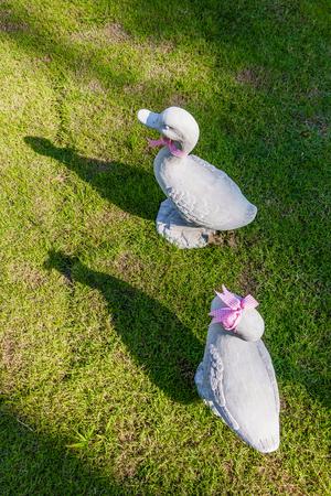 identical: White ducks decoration sculpture setting on green grass