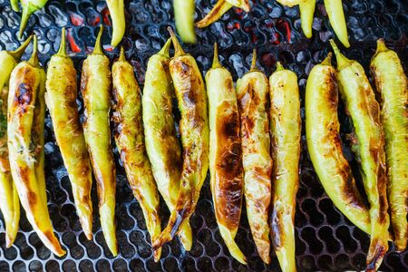 pimientos: Fresh chili peppers roasting over a charcoal fire. Foto de archivo