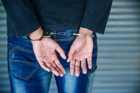 Male hands locked in handcuffs, Outlaws hands in handcuffs
