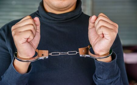 outlaws: Male hands locked in handcuffs, Outlaws hands in handcuffs