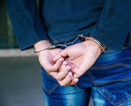 Male hands locked in handcuffs, Outlaw's hands in handcuffs Stock Photo - 67068456