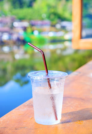 Plastic cup with cool water on wooden table and blurred background