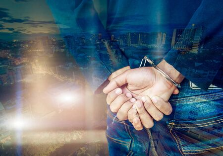handcuffs: Double exposure of male hands locked in handcuffs with city landscape background, with cross processing filter. Stock Photo