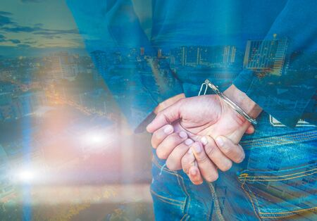 handcuffed: Double exposure of male hands locked in handcuffs with city landscape background, with cross processing filter. Stock Photo