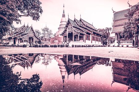 Phra Singh temple after rain and reflection on floor, Chiang Mai, Thailand,  Cross processing filter effect.