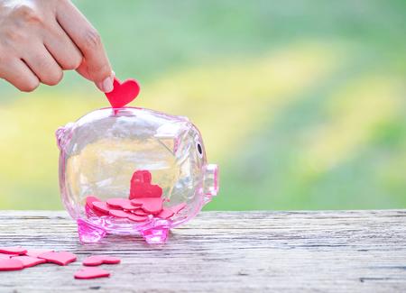 Hand die een rood hart in een spaarvarken, een Spaarvarken en een Rood Hart, een Concept liefde, Liefdadigheid en het Hulpwerk zet Stockfoto