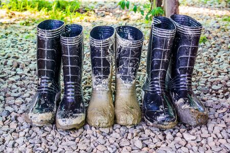 Muddy rubber boots on stone floor background
