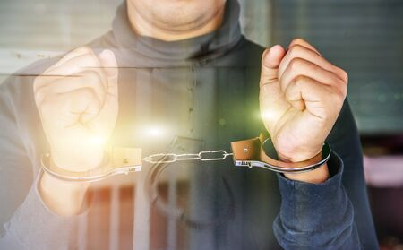 outlaws: Double exposure of male hands locked in handcuffs with jail bars background, Outlaws hands in handcuffs.