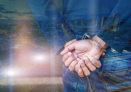outlaws: Double exposure of male hands locked in handcuffs with city landscape background, Outlaws hands in handcuffs