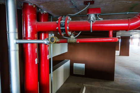 Red tubepipe system under ceiling in a parking lot , Pipe system hanging on ceiling.