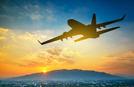 Silhouettes airplane is flying during on sunset background. Stock Photo