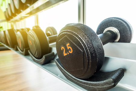 Image of dumbbells in gym Stock Photo
