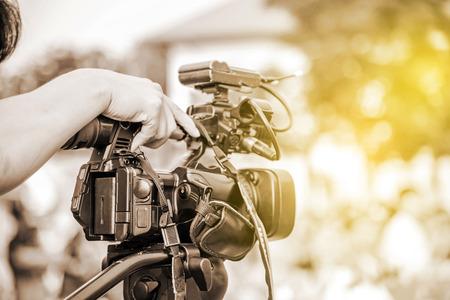 Videograaf neemt een videocamera en vervaagt het beeld van mensen op de achtergrond.
