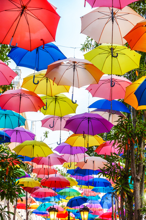 Multi-colored umbrellas background. Colorful umbrellas floating above the street. Street decoration. Stock Photo