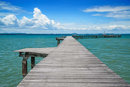 Beautiful wooden bridge in Thailand. Bridge extends into the sea. Stock Photo