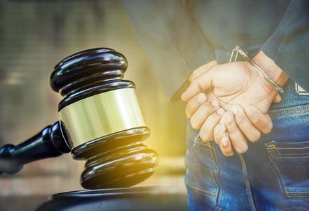 Justitie en wet concept. Houten hamer met gearresteerde man in handboeien Stockfoto