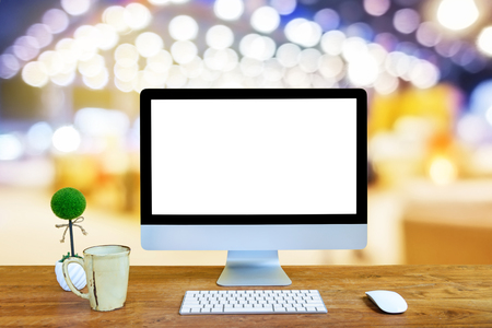 Computer Monitor with white screen, keyboard and mouse with coffee cup on the wooden table isolated blur background
