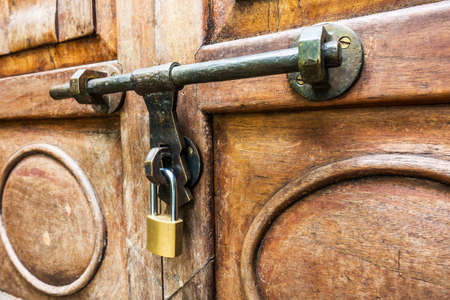 Old latch and padlock on a wooden door