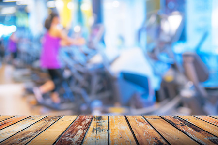 Empty top wooden table in fitness gym. For product display montage. Stock Photo