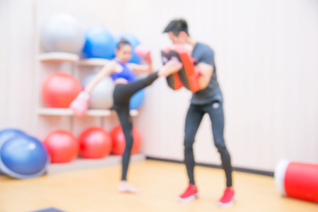Blurred Female practicing boxing. Fit woman and her trainer boxing indoors the gym.
