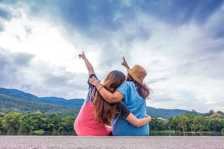 Mother and daughter hugging each other outdoors and point to the sky.