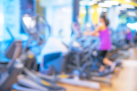 Blurred background of woman running in fitness center or health club with blurry sports exercise equipment