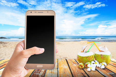 Young woman holding smart phone at beach in summer,  Summer holiday concept.