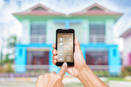 Hand using smart phone as smart home control application over blurred house background, smart home concept Stock Photo