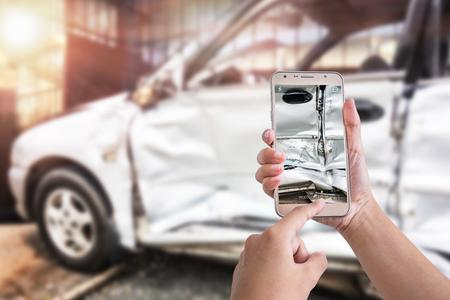 여자 차고에서 자동차 충돌에 의해 손상 사진을 찍는 스마트 전화를 사용 하여