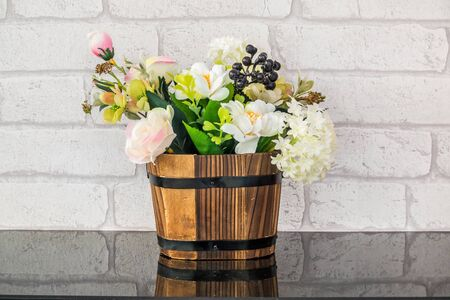 Decoration artificial flower in the pot with white brick background