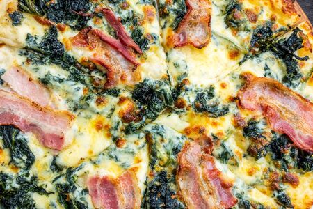 Pizza with bacon ham and spinach on wooden table. Stock Photo