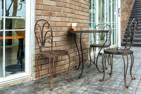 Metal chairs and table, iron chairs and table in front of the door. Stock Photo