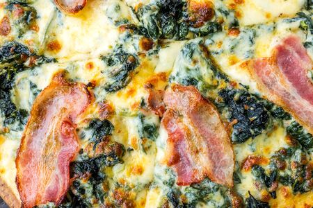 Pizza with bacon ham, sausage and spinach on wooden table.