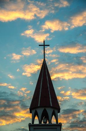 A silhouette of a church steeple in sunrise.