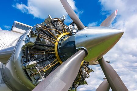 Close up view of airplane biplane with piston engine and propeller on a cloudy sky background