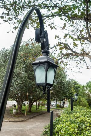 Vintage lanterns and pole in the garden park. Electrical light in the night.Garden design and decoration concept. Stock Photo