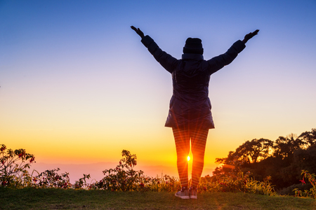 Silhouette of woman arms up outstretched for praying with sunbeam on hill. Christian praise on hill at sunset. Stock Photo