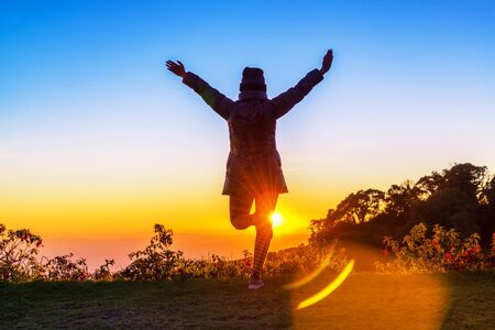 Silhouette happy celebrating winning success woman at sunset standing elated with arms raised up above her head. Strong confidence woman standing alone under beautiful sunset. Stock Photo