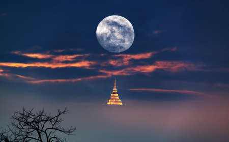 Supermoon. Full moon with a deep blue sky, misty and pagoda at night. View of a big moon, Moonrise in Thailand Stock Photo