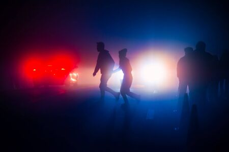 Silhouette of a couple hold hand walking across the street through the morning mist. Stock Photo