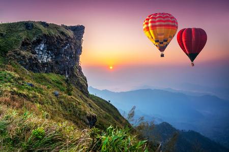 朝、フーチファ国立公園の山の上を飛ぶカラフルな熱気球。チェンライ県(タイ)