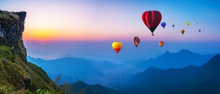 Colorful hot air balloons flying over mountain with sunrise at at phucheefa mountain. Chiang Rai Province, Thailand Banque d'images