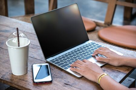 Young hipster womans hands busy using her laptop on wooden table with smart phone in a coffee shop   Stock Photo